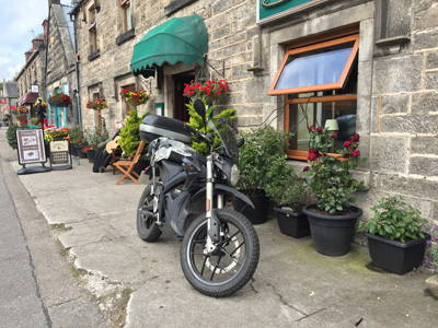 John Chivers' Zero DSR electric motorcycle charging outside the Sutherland Inn, Brora.