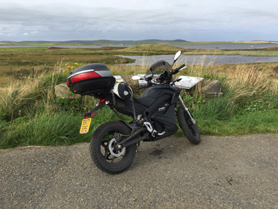 John Chivers' Zero DSR electric motorcycle in front of view across Loch of Harray on Orkney.